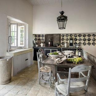 Inspiration pour une cuisine américaine rustique en L de taille moyenne avec un placard à porte plane, des portes de placard noires, une crédence multicolore et aucun îlot.