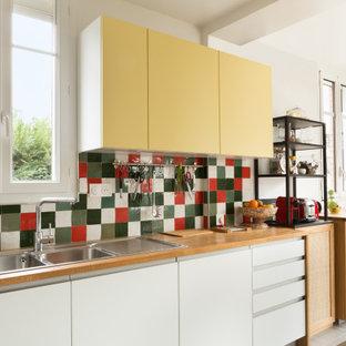 パリの広いコンテンポラリースタイルのおしゃれなキッチン (白いキャビネット、木材カウンター、マルチカラーのキッチンパネル、テラコッタタイルのキッチンパネル、テラコッタタイルの床、アイランドなし、グレーの床、ドロップインシンク、フラットパネル扉のキャビネット、茶色いキッチンカウンター) の写真