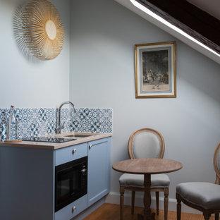 Idée de décoration pour une petite cuisine ouverte linéaire tradition avec un évier encastré, un placard à porte shaker, des portes de placard bleues, une crédence bleue, une crédence en mosaïque, aucun îlot, un sol marron et un plan de travail beige.