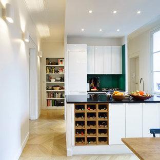 Réalisation d'une grand cuisine ouverte parallèle design avec des portes de placard blanches et un îlot central.