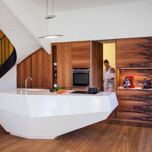 Idee per una grande cucina minimal con lavello integrato, ante marroni, pavimento in legno massello medio e isola
