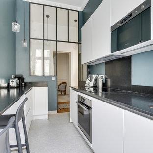 Foto di una cucina lineare design chiusa e di medie dimensioni con lavello sottopiano, ante a filo, ante bianche, top in quarzite, paraspruzzi nero, elettrodomestici in acciaio inossidabile, pavimento alla veneziana, pavimento beige e top nero