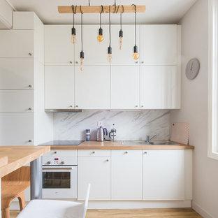 Cette photo montre une cuisine scandinave avec un évier posé, un placard à porte plane, des portes de placard blanches, un plan de travail en bois, une crédence blanche, une crédence en marbre, un électroménager blanc, un sol en bois clair et un sol beige.