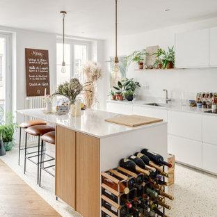 パリの中くらいの北欧スタイルのおしゃれなキッチン (アンダーカウンターシンク、フラットパネル扉のキャビネット、白いキャビネット、テラゾーの床、ベージュの床、白いキッチンカウンター) の写真