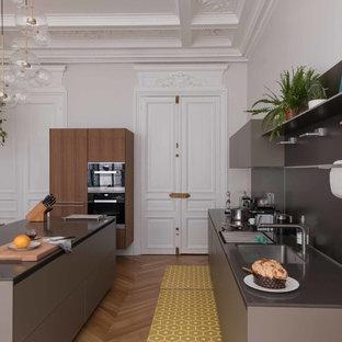 Aménagement d'une cuisine parallèle classique avec un évier encastré, un placard à porte plane, des portes de placard grises, une crédence grise, un électroménager noir, un sol en bois clair, un îlot central, un sol marron et un plan de travail gris.
