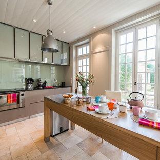 Cette image montre une grande cuisine américaine linéaire minimaliste avec des portes de placard grises, une crédence en feuille de verre et un îlot central.