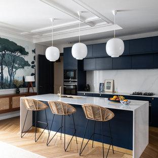 パリの広いコンテンポラリースタイルのおしゃれなキッチン (フラットパネル扉のキャビネット、淡色無垢フローリング、アンダーカウンターシンク、青いキャビネット、珪岩カウンター、白いキッチンパネル、クオーツストーンのキッチンパネル、パネルと同色の調理設備、白いキッチンカウンター) の写真