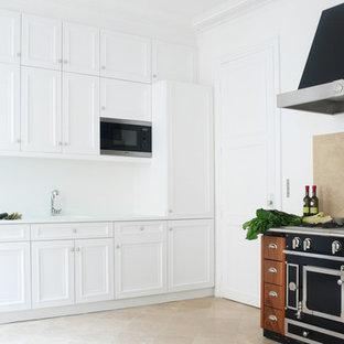 Idée de décoration pour une grande cuisine tradition en L fermée avec un évier intégré, un placard à porte affleurante, des portes de placard blanches, une crédence beige, un électroménager noir, un sol en travertin et une crédence en carreau de céramique.