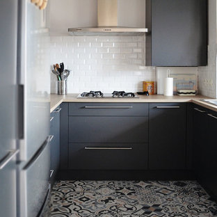 Photo of a mid-sized midcentury u-shaped open plan kitchen in Lyon with an integrated sink, beaded inset cabinets, grey cabinets, laminate benchtops, white splashback, subway tile splashback, stainless steel appliances, cement tiles, no island, multi-coloured floor and brown benchtop.