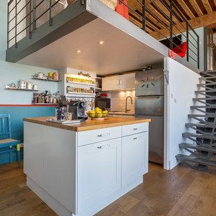 リヨンのインダストリアルスタイルのおしゃれなキッチン (シェーカースタイル扉のキャビネット、白いキャビネット、木材カウンター、白いキッチンパネル、サブウェイタイルのキッチンパネル、シルバーの調理設備の、無垢フローリング、茶色い床、ベージュのキッチンカウンター) の写真