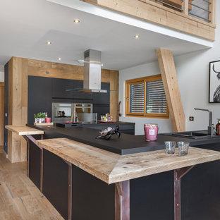 Aménagement d'une cuisine ouverte montagne avec un évier posé, un placard à porte plane, des portes de placard noires, un sol en bois clair, un îlot central et un plan de travail noir.