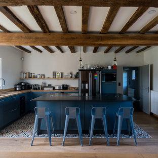 Inspiration pour une cuisine rustique en L avec un placard à porte plane, des portes de placard bleues, un plan de travail en bois, un électroménager noir, un îlot central, un sol multicolore et un plan de travail marron.
