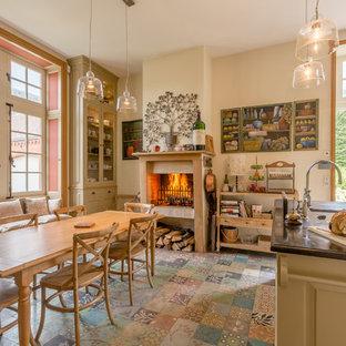 Réalisation d'une cuisine américaine champêtre avec un îlot central et un sol multicolore.