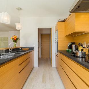 Inspiration pour une cuisine ouverte parallèle design de taille moyenne avec un évier 2 bacs, un placard à porte plane, des portes de placard en bois brun, une crédence métallisée, une crédence en dalle métallique, un sol en bois clair et une péninsule.