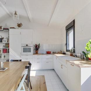 Aménagement d'une cuisine américaine contemporaine en L avec un évier de ferme, un placard à porte plane, des portes de placard blanches, un plan de travail en bois, une crédence blanche, une crédence en carreau de verre, un électroménager blanc, un sol blanc et un plan de travail beige.