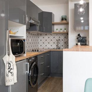 Пример оригинального дизайна интерьера: маленькая угловая кухня в скандинавском стиле с обеденным столом, накладной раковиной, фасадами с декоративным кантом, серыми фасадами, столешницей из ламината, серым фартуком, фартуком из цементной плитки, техникой под мебельный фасад, полом из фанеры, бежевым полом и бежевой столешницей