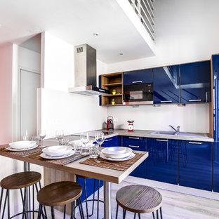 Idées déco pour une cuisine américaine contemporaine en U de taille moyenne avec un évier 1 bac, des portes de placard bleues, un plan de travail en stratifié, une crédence beige, un électroménager encastrable, un sol en vinyl, un placard à porte plane et aucun îlot.