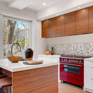 Réalisation d'une cuisine design avec un placard à porte plane, des portes de placard blanches, une crédence multicolore, une crédence en mosaïque, un électroménager de couleur, un sol en bois clair, un îlot central, un sol beige et un plan de travail blanc.