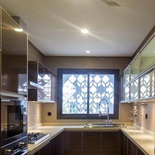Inspiration pour une cuisine minimaliste en U fermée et de taille moyenne avec un évier 3 bacs, un placard à porte vitrée, des portes de placard marrons, un plan de travail en quartz, une crédence beige, une crédence en carreau de porcelaine, un électroménager en acier inoxydable, un sol en carrelage de porcelaine et un sol beige.