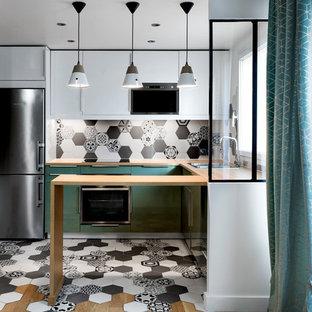 パリの中サイズの地中海スタイルのおしゃれなキッチン (ドロップインシンク、フラットパネル扉のキャビネット、白いキャビネット、木材カウンター、マルチカラーのキッチンパネル、セメントタイルのキッチンパネル、セメントタイルの床、マルチカラーの床、ベージュのキッチンカウンター) の写真