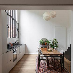 Idée de décoration pour une cuisine américaine linéaire design avec un évier encastré, un placard à porte plane, des portes de placard grises, un sol en bois clair, un sol beige et un plan de travail noir.