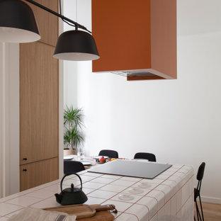 パリの中くらいの北欧スタイルのおしゃれなキッチン (一体型シンク、インセット扉のキャビネット、淡色木目調キャビネット、タイルカウンター、グレーのキッチンパネル、パネルと同色の調理設備、テラコッタタイルの床、茶色い床、白いキッチンカウンター) の写真
