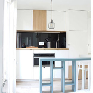 Design ideas for a small contemporary galley open plan kitchen in Paris with a single-bowl sink, beaded inset cabinets, white cabinets, wood benchtops, black splashback, glass tile splashback, stainless steel appliances, laminate floors, with island, brown floor and brown benchtop.