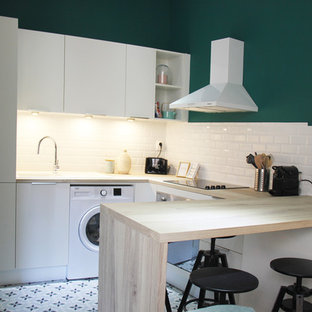 Inspiration for a mid-sized midcentury u-shaped open plan kitchen in Lyon with an undermount sink, beaded inset cabinets, white cabinets, wood benchtops, white splashback, ceramic splashback, white appliances, cement tiles, no island, blue floor and beige benchtop.