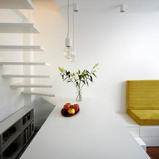 Idée de décoration pour une petite cuisine ouverte parallèle design avec un placard sans porte, des portes de placard blanches et un îlot central.