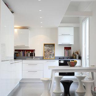 Idée de décoration pour une cuisine américaine design en L de taille moyenne avec un évier posé, un placard à porte plane, des portes de placard blanches et un électroménager encastrable.