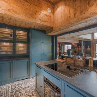 Inspiration pour une cuisine ouverte chalet en L avec un placard à porte vitrée, des portes de placard bleues, une crédence grise, un électroménager noir, un îlot central et un sol multicolore.