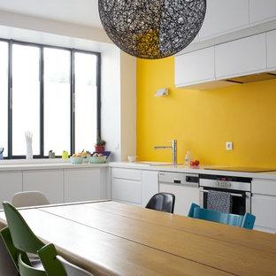 Idées déco pour une grand cuisine américaine contemporaine en L avec un placard à porte plane, des portes de placard blanches, un électroménager en acier inoxydable, aucun îlot et une crédence jaune.