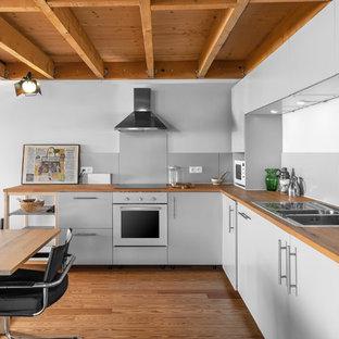 Idée de décoration pour une cuisine américaine urbaine en L avec un plan de travail en bois, un sol en bois brun, aucun îlot, un évier 2 bacs, un placard à porte plane, des portes de placard grises, un sol marron et un plan de travail marron.