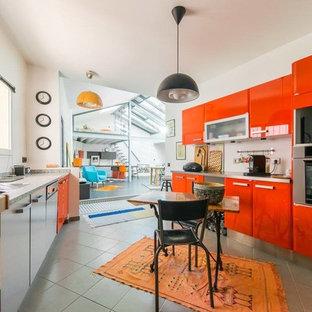 リールの広いエクレクティックスタイルのおしゃれなキッチン (白いキッチンパネル、シルバーの調理設備、アイランドなし、グレーの床、ドロップインシンク、フラットパネル扉のキャビネット、赤いキャビネット、ステンレスカウンター、セメントタイルの床) の写真