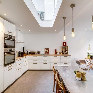 Immagine di una cucina design con ante lisce, ante bianche, top in legno, elettrodomestici in acciaio inossidabile, pavimento in cemento, nessuna isola e pavimento grigio