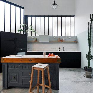 Exemple d'une très grand cuisine ouverte industrielle en L avec un évier 1 bac, des portes de placard noires, un plan de travail en stratifié, une crédence blanche, une crédence en carreau de céramique, un électroménager noir, béton au sol, un îlot central, un sol gris, un plan de travail blanc et un placard à porte plane.