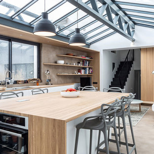 Design ideas for a medium sized urban single-wall kitchen/diner in Paris with wood worktops, an island, beige worktops, a double-bowl sink, flat-panel cabinets, white cabinets, brown splashback, stainless steel appliances and brown floors.