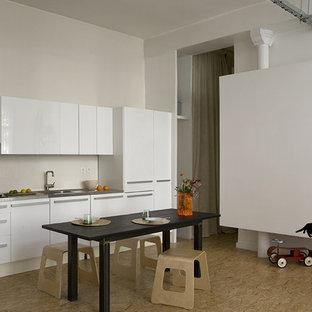 Réalisation d'une grande cuisine américaine linéaire design avec un évier intégré, un placard à porte plane, des portes de placard blanches, un plan de travail en inox et aucun îlot.