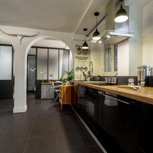 Inspiration pour une grande cuisine ouverte linéaire design avec des portes de placard noires et aucun îlot.
