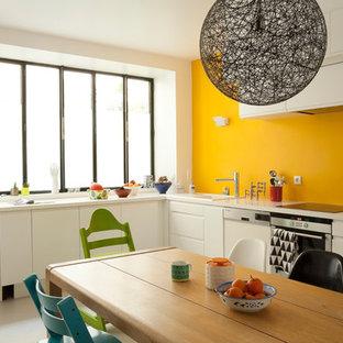 Exemple d'une grand cuisine américaine tendance en L avec un placard à porte plane, des portes de placard blanches, un électroménager en acier inoxydable et aucun îlot.