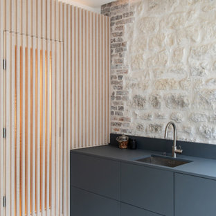 パリの小さいエクレクティックスタイルのおしゃれなキッチン (アンダーカウンターシンク、インセット扉のキャビネット、グレーのキャビネット、ラミネートカウンター、ベージュキッチンパネル、ライムストーンのキッチンパネル、シルバーの調理設備、コンクリートの床、アイランドなし、グレーの床、グレーのキッチンカウンター) の写真