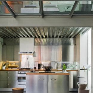 Inredning av ett industriellt mellanstort kök, med släta luckor, skåp i rostfritt stål, stänkskydd med metallisk yta, rostfria vitvaror och en köksö