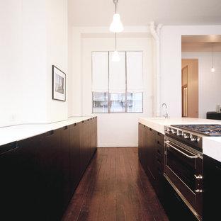 Idées déco pour une cuisine ouverte parallèle contemporaine de taille moyenne avec des portes de placard en bois sombre et un îlot central.