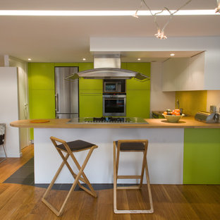 Mid-sized galley open plan kitchen in Paris with a double-bowl sink, beaded inset cabinets, green cabinets, wood benchtops, yellow splashback, glass tile splashback, stainless steel appliances, slate floors, with island and black floor.