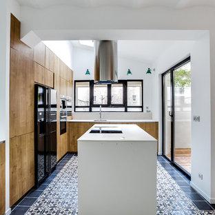 パリの大きいインダストリアルスタイルのおしゃれなキッチン (淡色木目調キャビネット、ラミネートカウンター、ベージュキッチンパネル、ボーダータイルのキッチンパネル、黒い調理設備、セメントタイルの床、アンダーカウンターシンク、インセット扉のキャビネット、黒い床) の写真