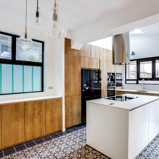 パリの大きいインダストリアルスタイルのおしゃれなキッチン (黒い調理設備、セメントタイルの床、アンダーカウンターシンク、インセット扉のキャビネット、淡色木目調キャビネット、ラミネートカウンター、ベージュキッチンパネル、ボーダータイルのキッチンパネル、黒い床) の写真