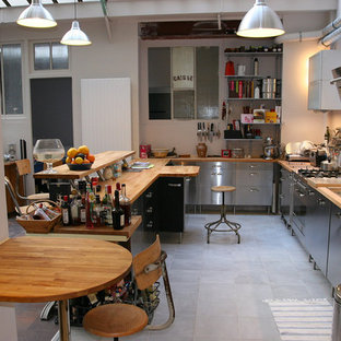 Inspiration for a mid-sized industrial u-shaped ceramic floor eat-in kitchen remodel in Marseille with flat-panel cabinets, stainless steel cabinets, wood countertops, a double-bowl sink and a peninsula