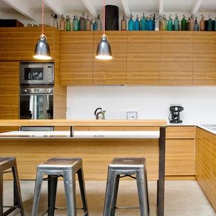 Réalisation d'une cuisine américaine design en L de taille moyenne avec un îlot central, un évier encastré, un placard à porte affleurante, des portes de placard en bois brun, un plan de travail en quartz modifié, une crédence blanche, un électroménager encastrable et béton au sol.