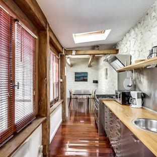 Inspiration pour une grand cuisine américaine linéaire rustique avec un évier 1 bac, un placard à porte plane, une façade en inox, un plan de travail en bois, une crédence métallisée, un électroménager en acier inoxydable, un sol en bois brun et aucun îlot.