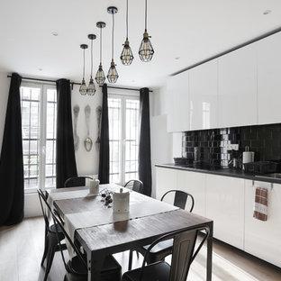 Cette image montre une cuisine américaine design avec un évier posé, un placard à porte plane, des portes de placard blanches, une crédence noire, un sol en bois clair et un sol beige.